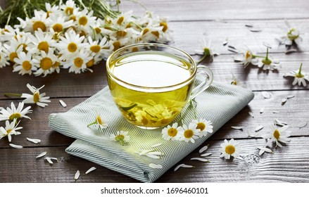 Chamomile herbal tea with flower buds nearby on wooden table with textile and camomile bouquet, closeup, copy space, healthy herbal drinks and natural healer concept
