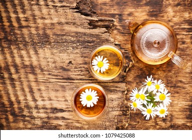 Chamomile herbal tea in a teapot and cup and chamomile flowers on a wooden table, top view