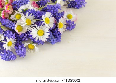 Chamomile and hyacinth flowers on a wooden table