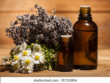 Chamomile and lavender essential oil on wooden background