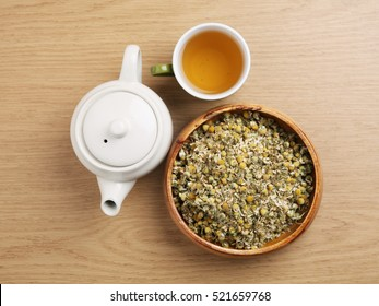 Chamomile tea with dried chamomile flowers on wooden table.