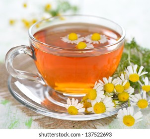 Chamomile tea in a glass cup on a white table
