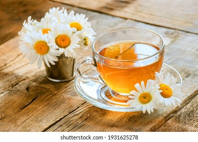 chamomile tea on wooden background, transparent cup with warm aromatic drink, relaxation and detox