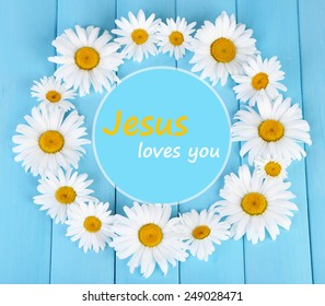 Chamomile wreath and text Jesus loves you on blue wooden background