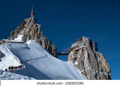 Chamonix, France - 30 Mars 2017: Line of offpiste skiers and ski tourers waiting to make their way down famous ridge (arete) on Aiguille du Midi to ski down Vallee Blanche.