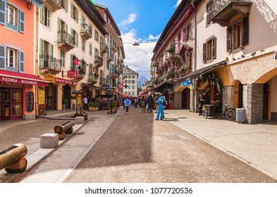 CHAMONIX-MONT-BLANC, FRANCE - APRIL 1, 2018 : Dr Paccard street in Chamonix with tourists walk in town. Chamonix is one of the oldest ski resorts in France.