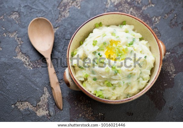 Champ or Irish potato puree with green onion, one of traditional meals for Saint Paddy's Day, elevated view on a brown stone background
