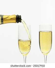 Champagne being poured into a flute, isolated on a white background.
