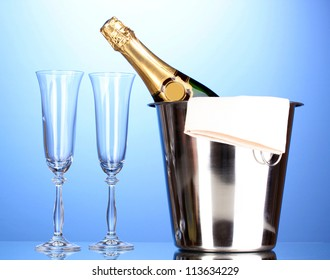 Champagne bottle in bucket with ice and glasses on blue background