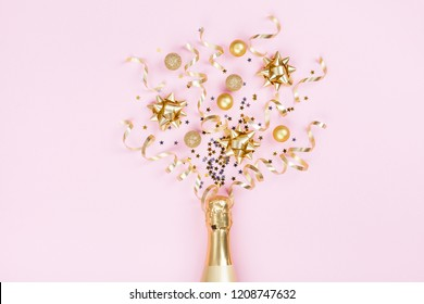 Champagne bottle with christmas decoration from confetti stars, golden balls and party streamers on pink background. Flat lay style.