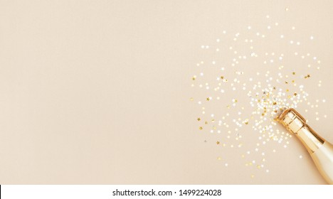 Champagne bottle with confetti stars on golden festive background. Christmas, birthday or wedding concept. Flat lay.