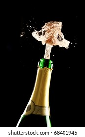 Champagne bottle with cork bursting out and spray