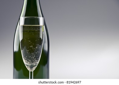 A champagne bottle and glass standing in front