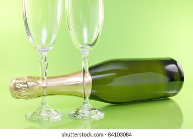 champagne bottle and glasses on green background.