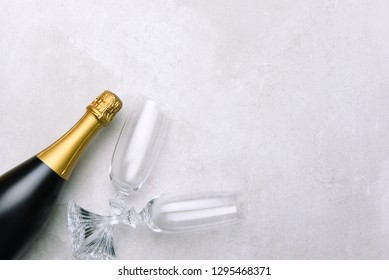 Champagne bottle and glasses on light gray surface. Horizontal format with copy space.