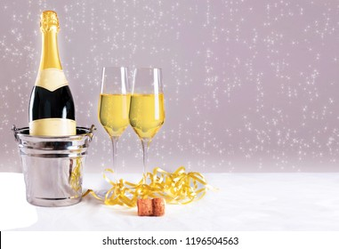Champagne bottle with glasses with stars in the background