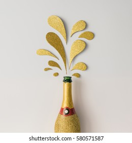 Champagne bottle with golden glittering splashes on white background. Flat lay. Minimal party concept.