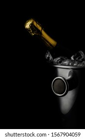 Champagne bottle and ice bucket on black background