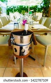 Champagne bottle opened inside a bucket to cool it, in a Mediterranean restaurant under vineyards.