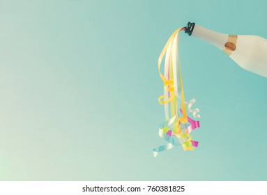 Champagne bottle with party streamers on bright blue background.  Party concept.