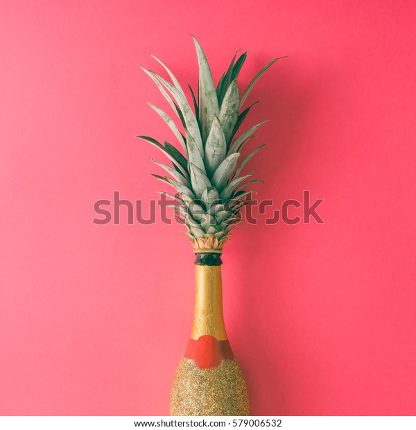Champagne bottle with pineapple leaves on pink background. Flat lay. Minimal party concept.