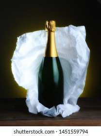 Champagne Bottle Still Life: A bottle with no label with tissue paper wrapping pulled back