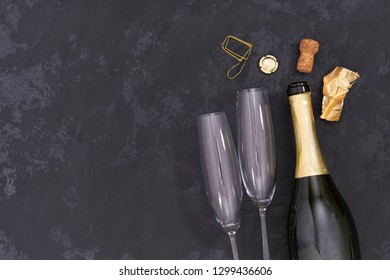 Champagne bottle and two empty glasses  on a black background Valentine's Day. Birthday. Wedding. Anniversary. Top view