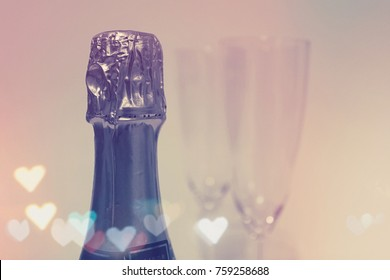 Champagne Bottle with Two Glasses in the Background and Heart Shaped Lens Flares