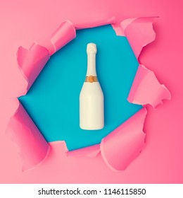 Champagne bottle with vivid pink torn paper. Burst hole background. Minimal abstract colorful wallpaper concept.