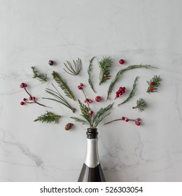 Champagne bottle with winter foliage on marble background. Flat lay. Party concept.