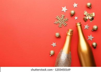 Champagne bottles with christmas decorations on red background