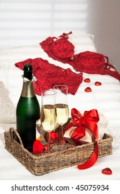 Champagne breakfast with heart shaped chocolates and gift with lacy lingerie on pillow