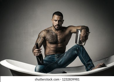 Champagne celebration. Handsome man with tattooed body on gray background. Sexy night party - young lovers. Fashion mans legs in jeans