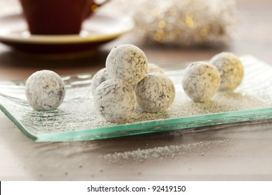 champagne chocolate truffles on glass plate, cup of coffee in background