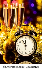 champagne with clock and christmas toys on blurred background