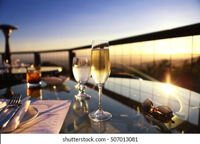 Champagne and cocktail glasses on glass table outdoor patio overlooking mountains at sunset
