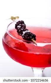 champagne cocktail at wineglass decorated with blackberry on white background