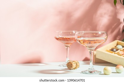 Champagne color or wine in glasses, box of white and dark chocolate candies on pink background bright light. Copy space.