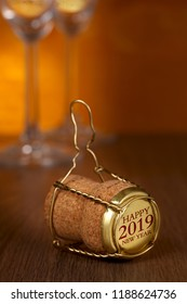 Champagne cork, 2019 on cap, two glasses on wooden background.