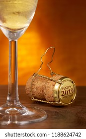 Champagne cork, 2019 on cap, glass in front, wooden background.