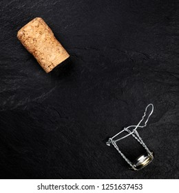 A champagne cork and closure, shot from the top on a black background, forming a frame with a place for text, a Christmas or New Year greeting card design template