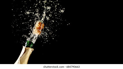 Champagne cork popping and splashing on black background