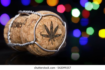 Champagne cork with the shape of a weed leaf burnt in and colorful blurry lights in the background.(series)