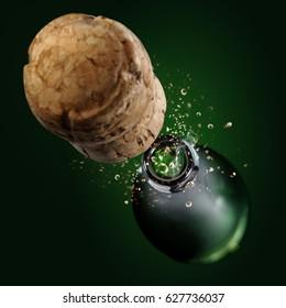 champagne cork  splash on green dark background and blurred green bottle