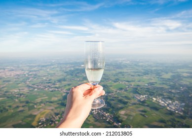 Champagne flute raised from hot air balloon
