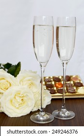 Champagne Flutes Filled with Champagne, Box of Chocolate and Bunch of White Roses on the background
