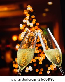 champagne flutes with golden bubbles make cheers on christmas lights decoration background, christmas atmosphere