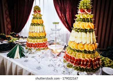 Champagne fountain and decorations from fruit on table setting at a wedding reception in restaurant
