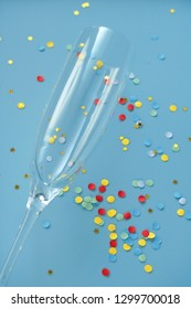 champagne glass and confetti on blue background