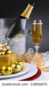 Champagne glass and ice bucket on a decorated holiday table with presents, ribbon and bells. Vertical format on a light to dark background.